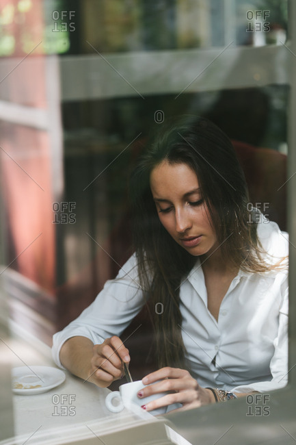 Beautiful Girl Sitting In A Cafe Drinking Coffee