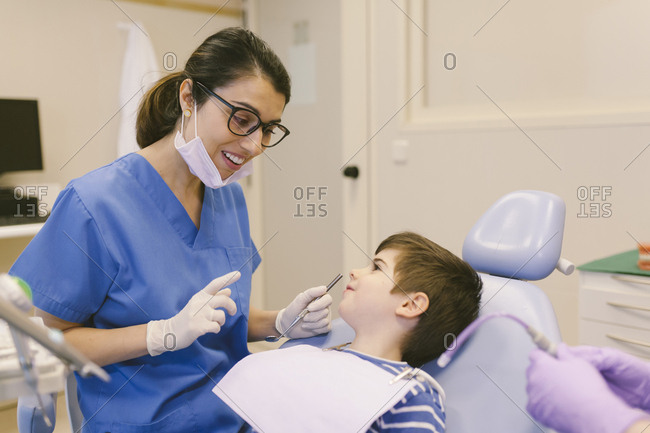 Woman dentist attending to a child in her office