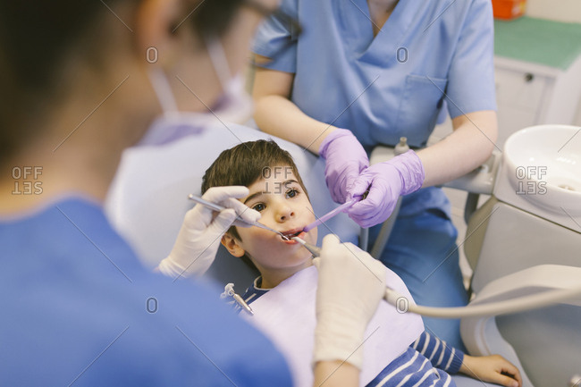 Woman dentist and her assistant attending to a child in her office