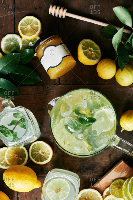 Fresh lemonade in glass jug with rosemary and mint and fresh lemons