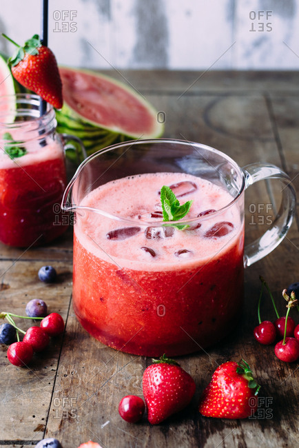 Glass pitcher filled with fresh juice from strawberries and grapefruit and watermelon