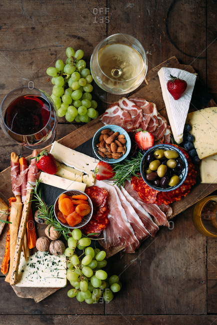 Cheese board with cured meat wine and fruit on rustic table