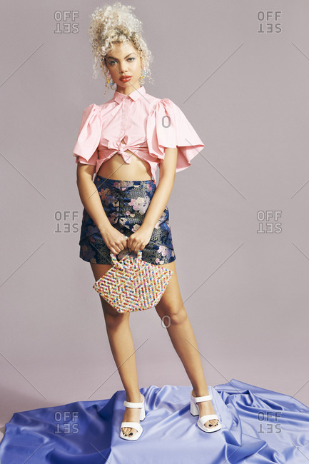 Portrait of a trendy multiracial woman posing with a colorful beaded bag