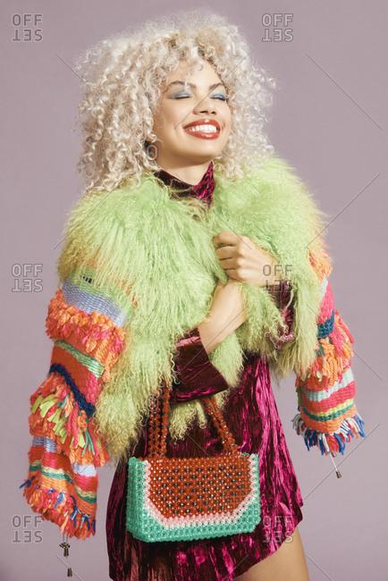 Stylish multiracial model happily holding onto her colorful coat