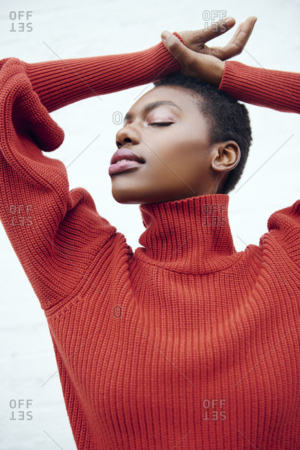 Young black woman with short brown hair poses in her red sweater