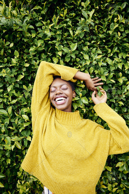 Young black woman with short brown hair poses in her yellow sweater