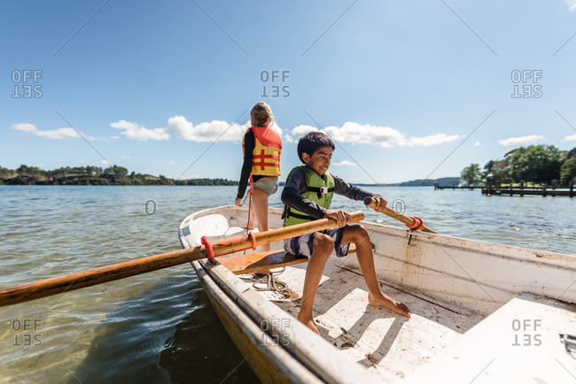 Two siblings in a rowboat on the lake in summer