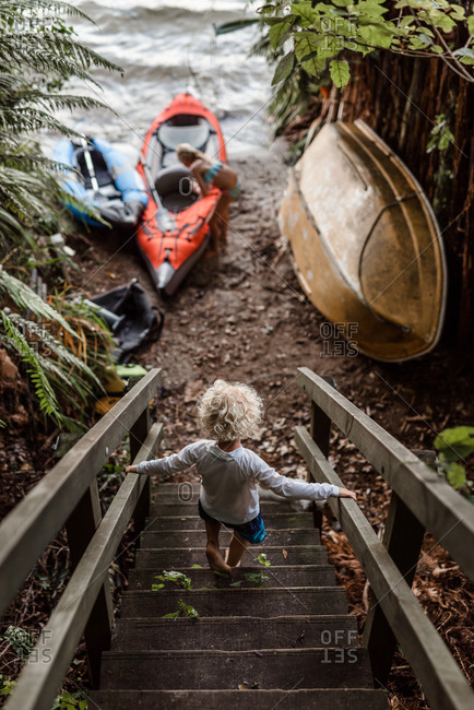 Young child climbs down wooden stairs towards kayak and lake