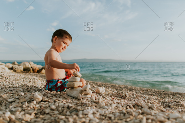 Child playing with stones on beach. Young boy wearing summer shorts stacking pebbles on beach on his own.