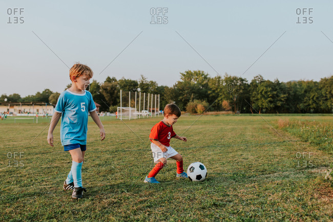 Children playing soccer. Full length of young boys in football dresses chasing ball on football pitch.