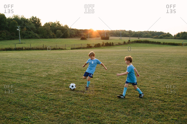 Children running after soccer ball. Front view of young boys in football dresses kicking ball on football pitch.