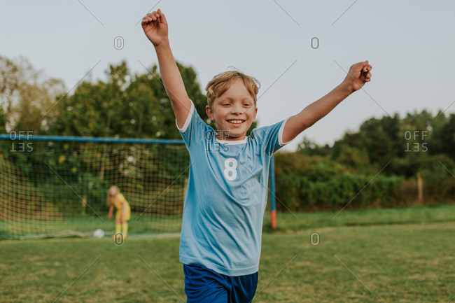 Children playing football outside on pitch. Happy young boy scoring goal during amateur soccer game.