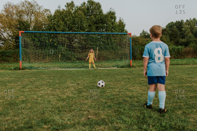 Back view of a child wearing football dress standing in front of goal practicing shooting. Full length of girl goalkeeper standing at goal and soccer player about to shoot ball.
