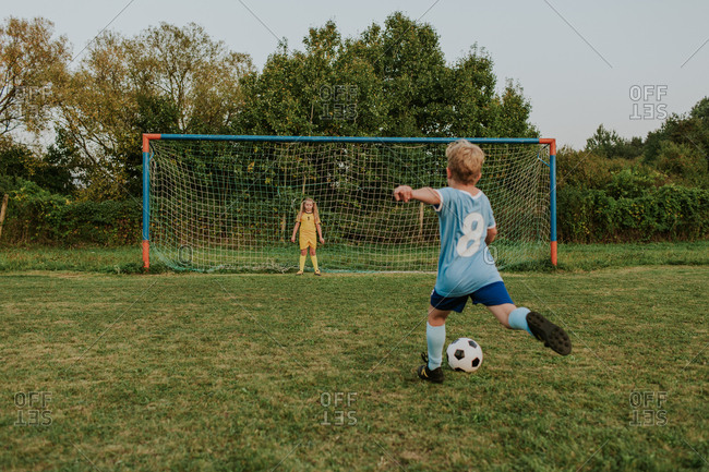 Back view of a child wearing football dress shooting ball in front of goal. Full length of girl goalkeeper standing at goal and soccer player kicking ball.