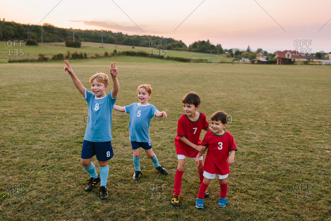 Children playing amateur football. Cheerful boys in soccer dresses having fun at training on pitch.
