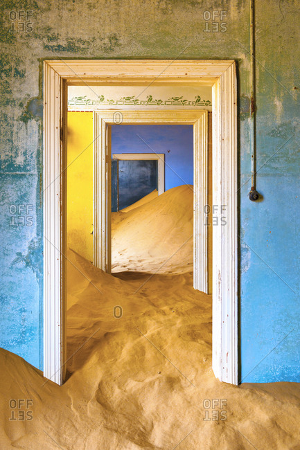 Africa, Namibia, Kolmanskop. Doorways and drifting sand in an abandoned diamond mining town.