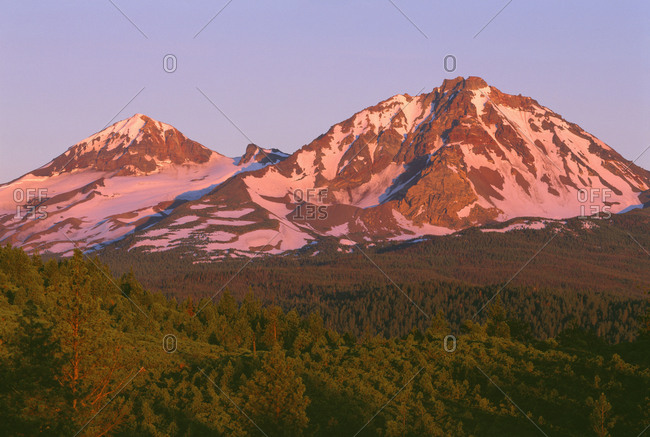 USA, Oregon, Deschutes National Forest. Sunrise reddens Middle Sister (left) and North Sister (right) in the Three Sisters Wilderness.