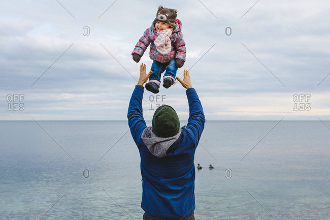 Father throws his baby girl in the air by the lake.