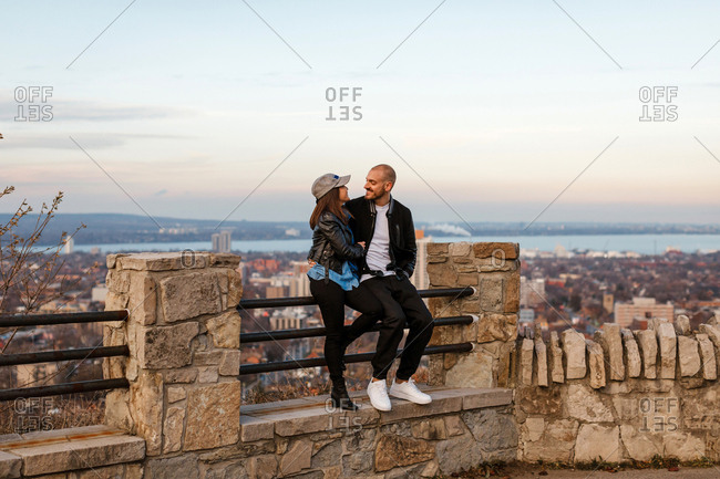 A couple sitting on a fence overlooking the city