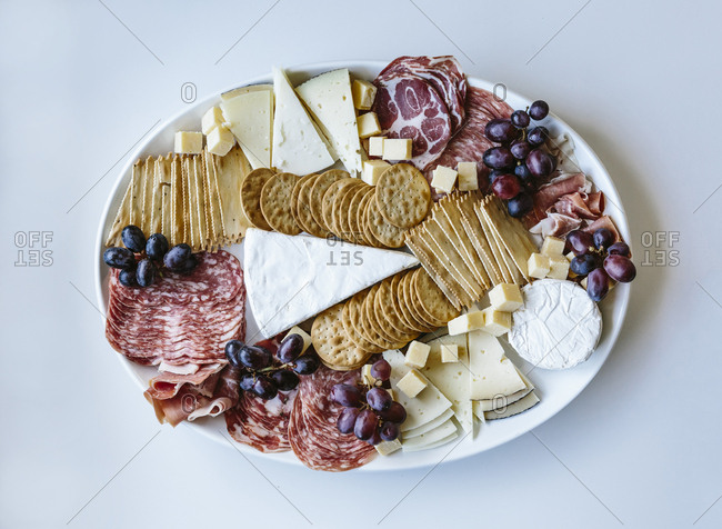 Top view of a white platter of cheese and meats and crackers on a white background