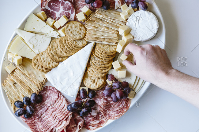 Top view of a white platter of cheese and meats and crackers on a white background with a hand grabbing a cheese