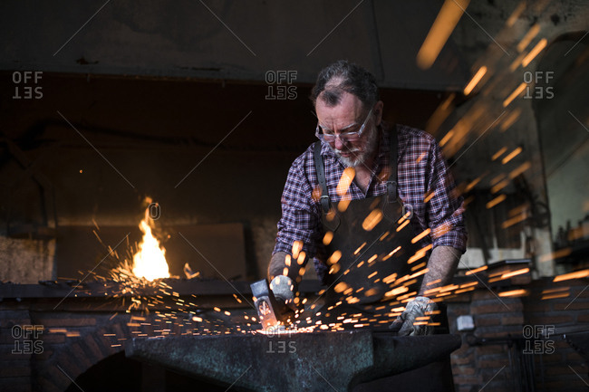 Blacksmith working with hammer at anvil in his workshop