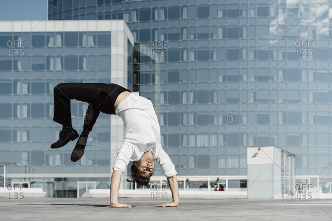 Artist doing handstand on roof terrace