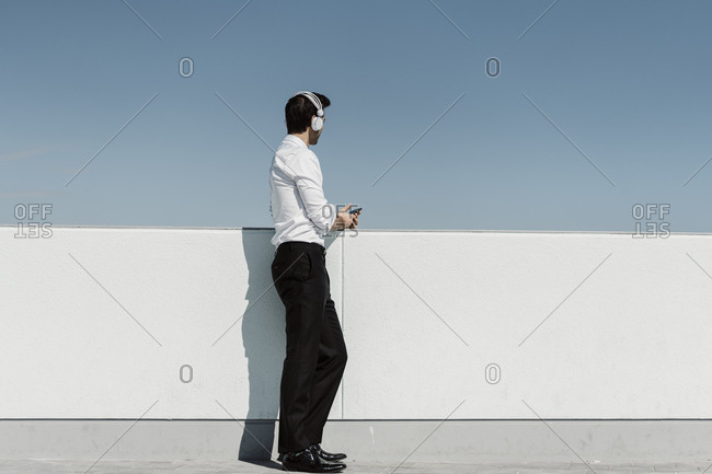 Businessman listening music with headphones and smartphone on roof terrace