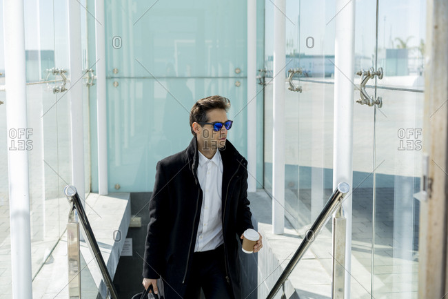 Portrait of businessman with sunglasses- coffee to go and baggage on stairs