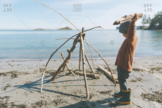 Boy playing on a the beach- building a drift wood fort
