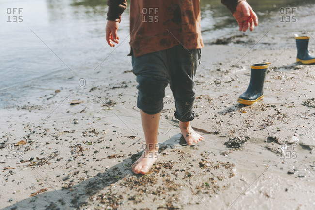 Boy playing on a the beach- walking barefoot in the mud