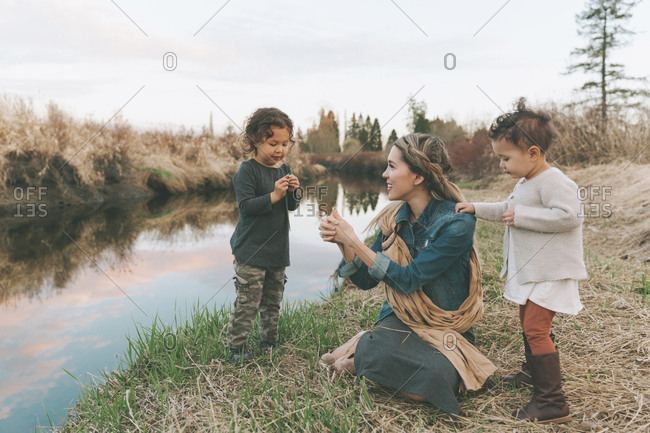 Mother and children playing with a grass blade at a river