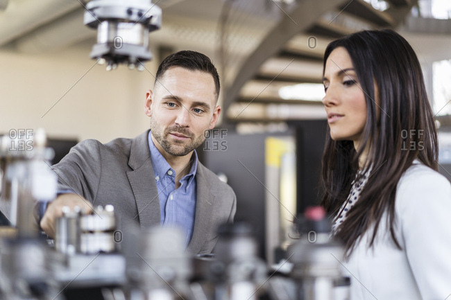 Businessman and businesswoman examining workpieces in factory