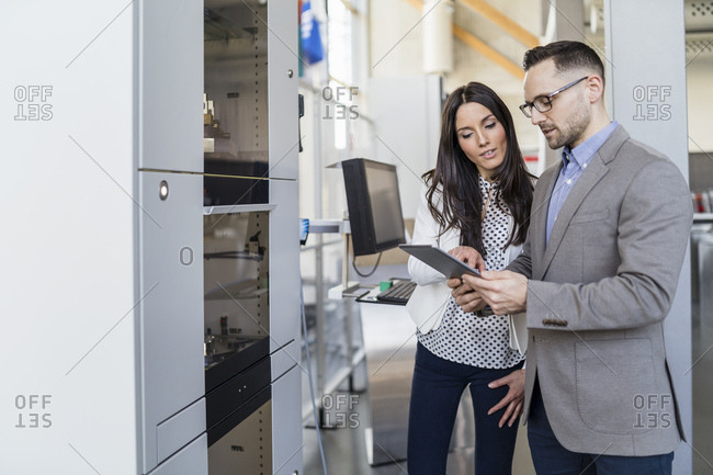 Businessman and businesswoman with talking in modern factory