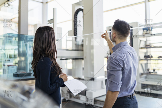 Rear view of businessman and businesswoman talking in modern factory