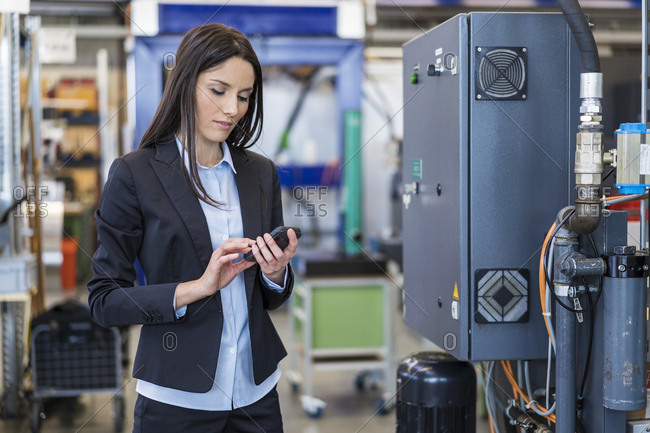 Businesswoman using cell phone in a factory