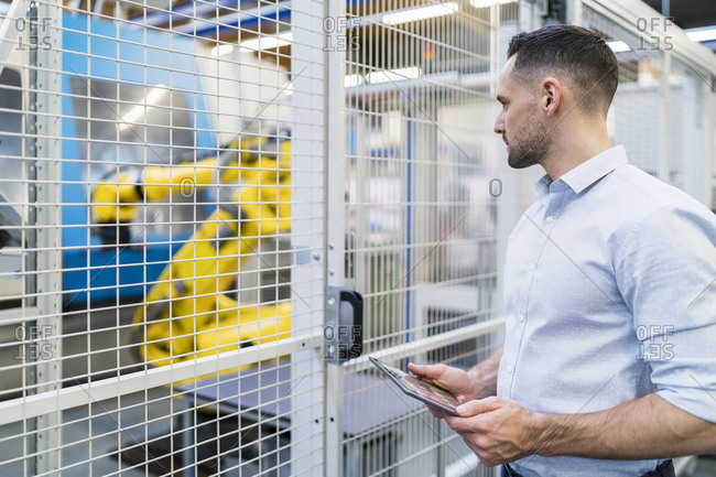 Businessman using tablet in a modern factory