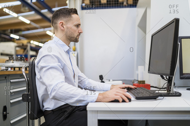 Businessman using computer at desk in a factory