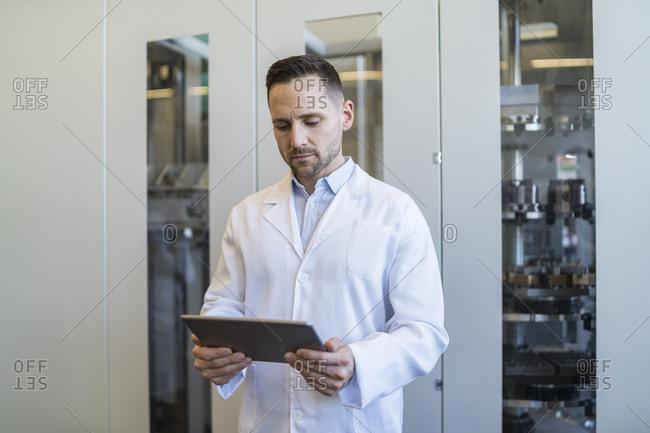 Man using tablet wearing lab coat in modern factory