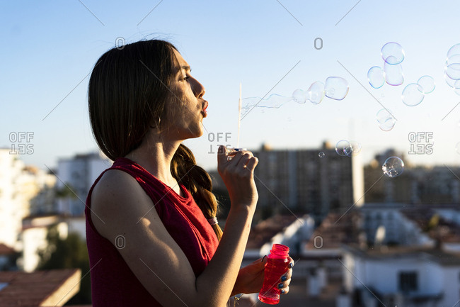 Teenage girl blowing soap bubbles on roof terrace in the city at sunset