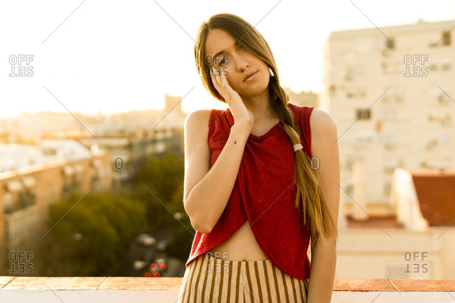 Portrait of teenage girl on roof terrace in the city at sunset