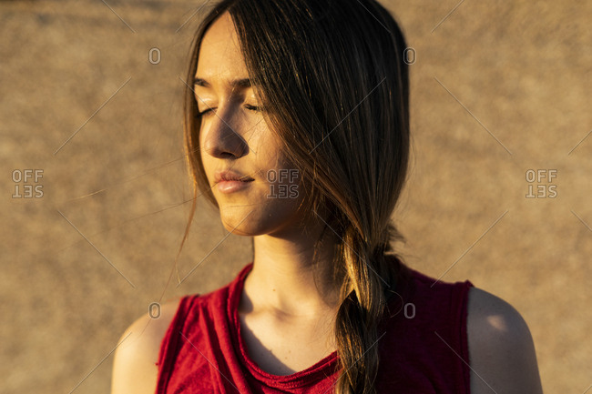 Portrait of teenage girl with closed eyes in sunlight