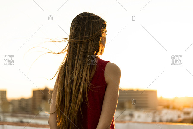 Rear view of teenage girl on roof terrace in the city at sunset
