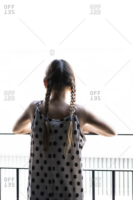 Rear view of girl wearing dotted dress looking from balcony