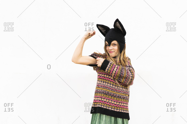 Portrait of girl flexing muscles in bat costume in front of white wall