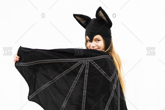Portrait of girl in bat costume spreading wings