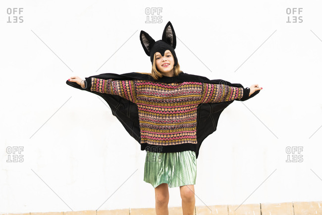 Portrait of girl in bat costume spreading wings in front of white wall