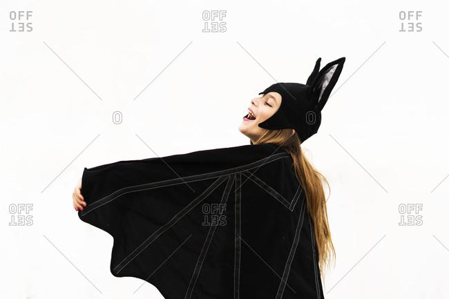 Happy girl in bat costume spreading wings