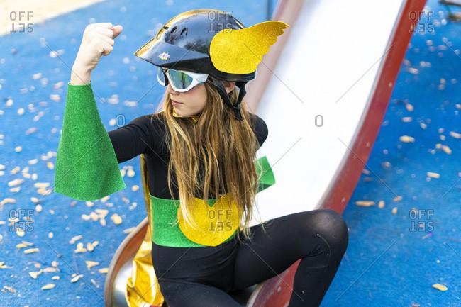 Girl in super heroine costume on playground slide flexing muscles