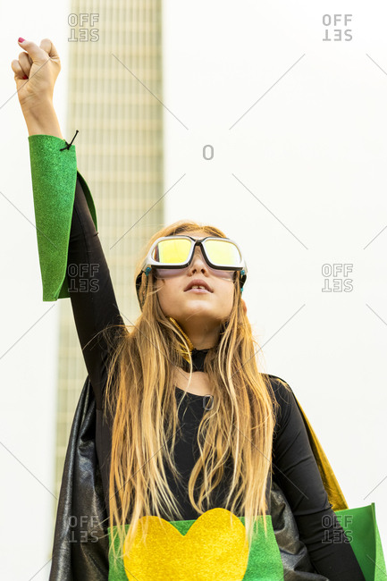 Girl posing in super heroine costume clenching fist